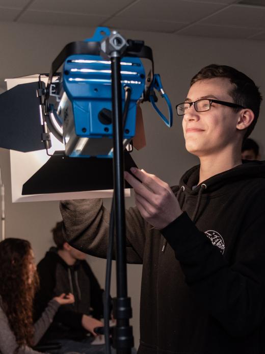 Male student adjusting a light on a film set