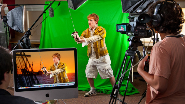 Male actor in front a green screen being filmed