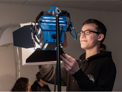 Male student adjusting the lighting on a film set
