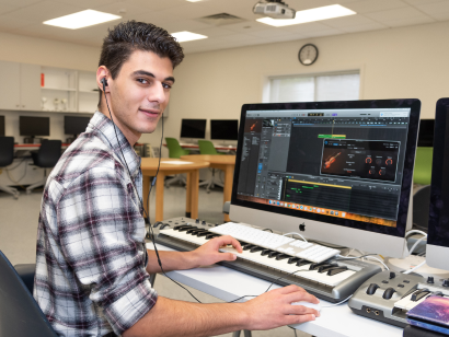 Male student creating music on the computer