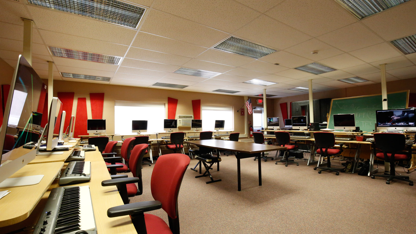 Computer lab with rolling chairs and desks and computers