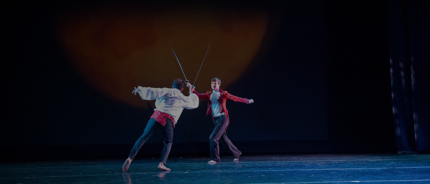 Two students sword fighting on stage
