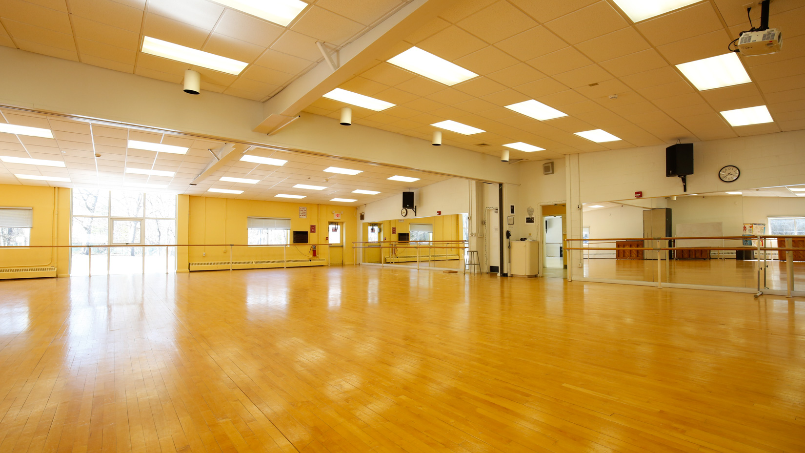 Large dance studio with mirrored walls and wooden floors