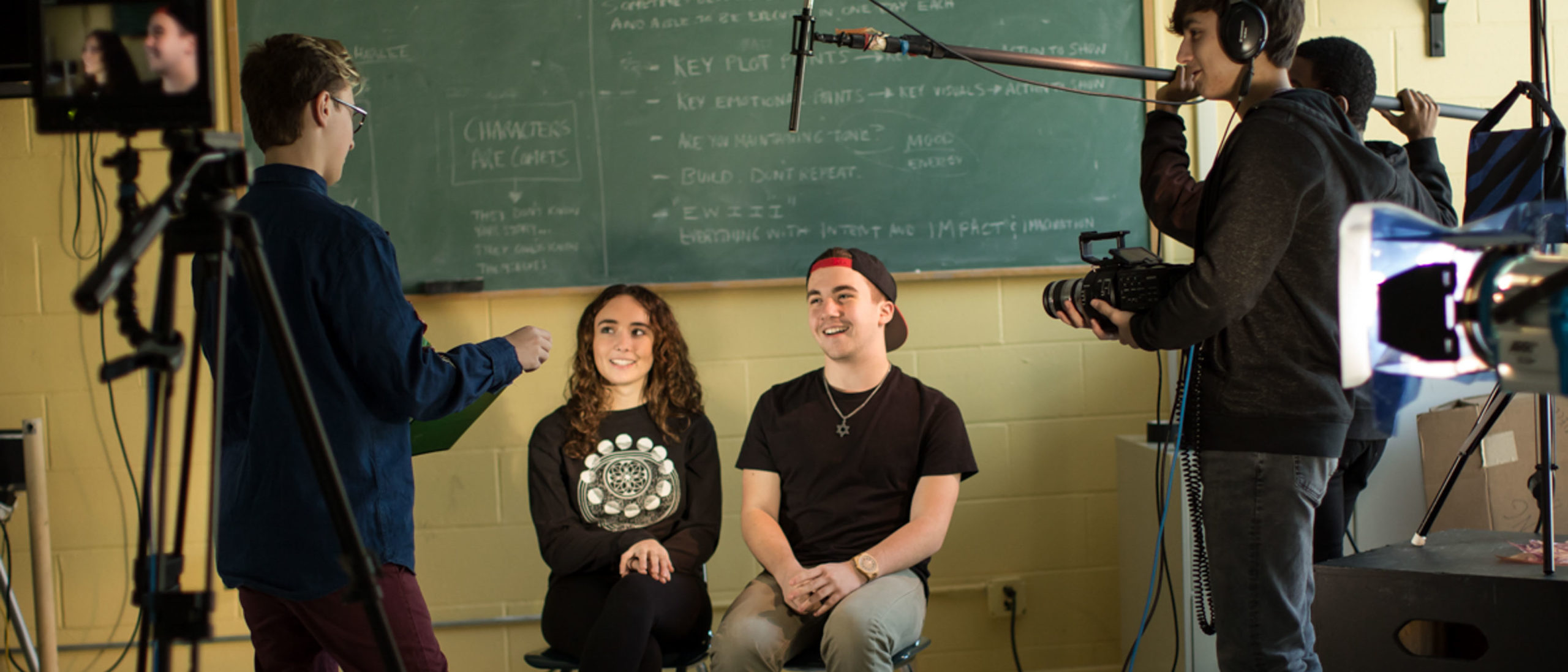Two students being interviews as film students film and direct them