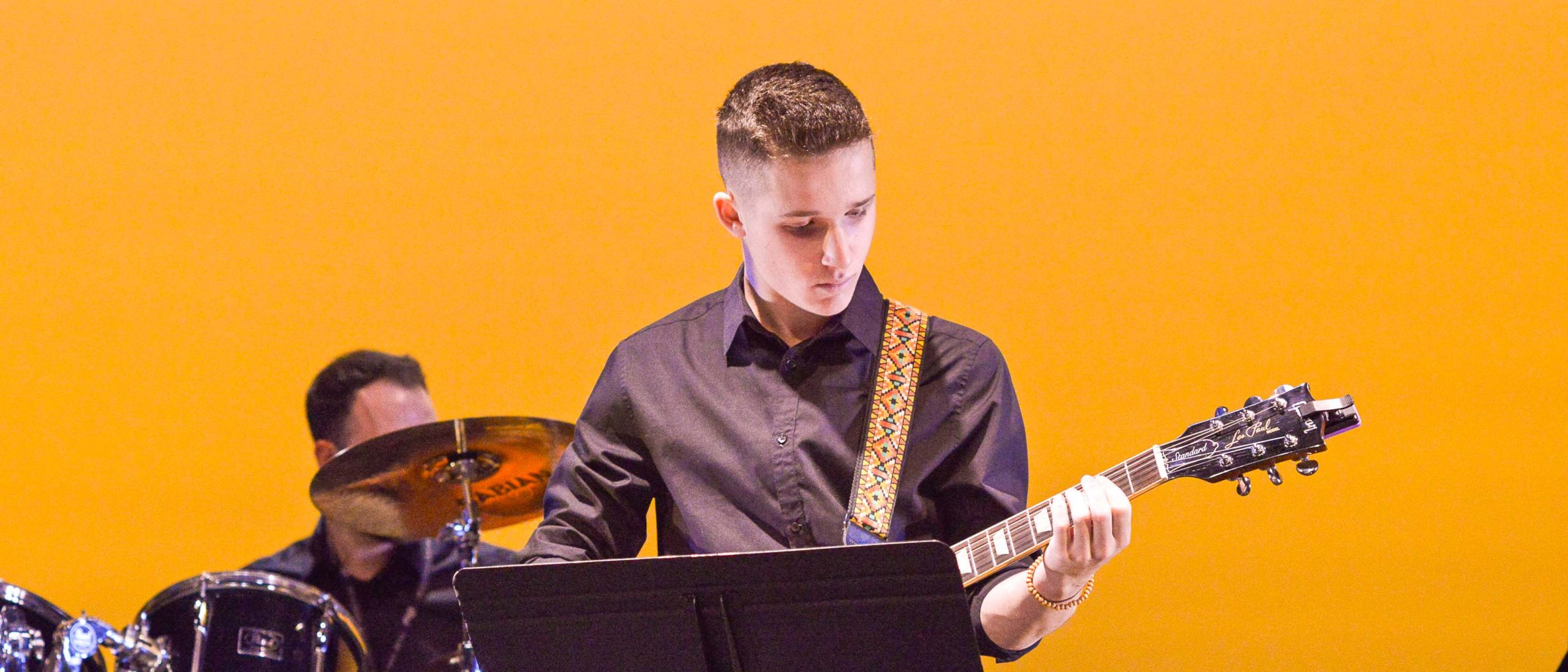 Boy student playing the guitar on stage