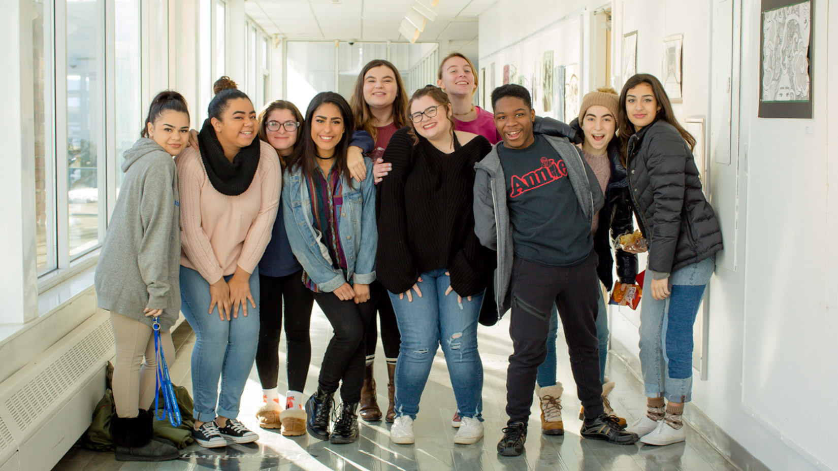 Group of students smiling together in the hallway