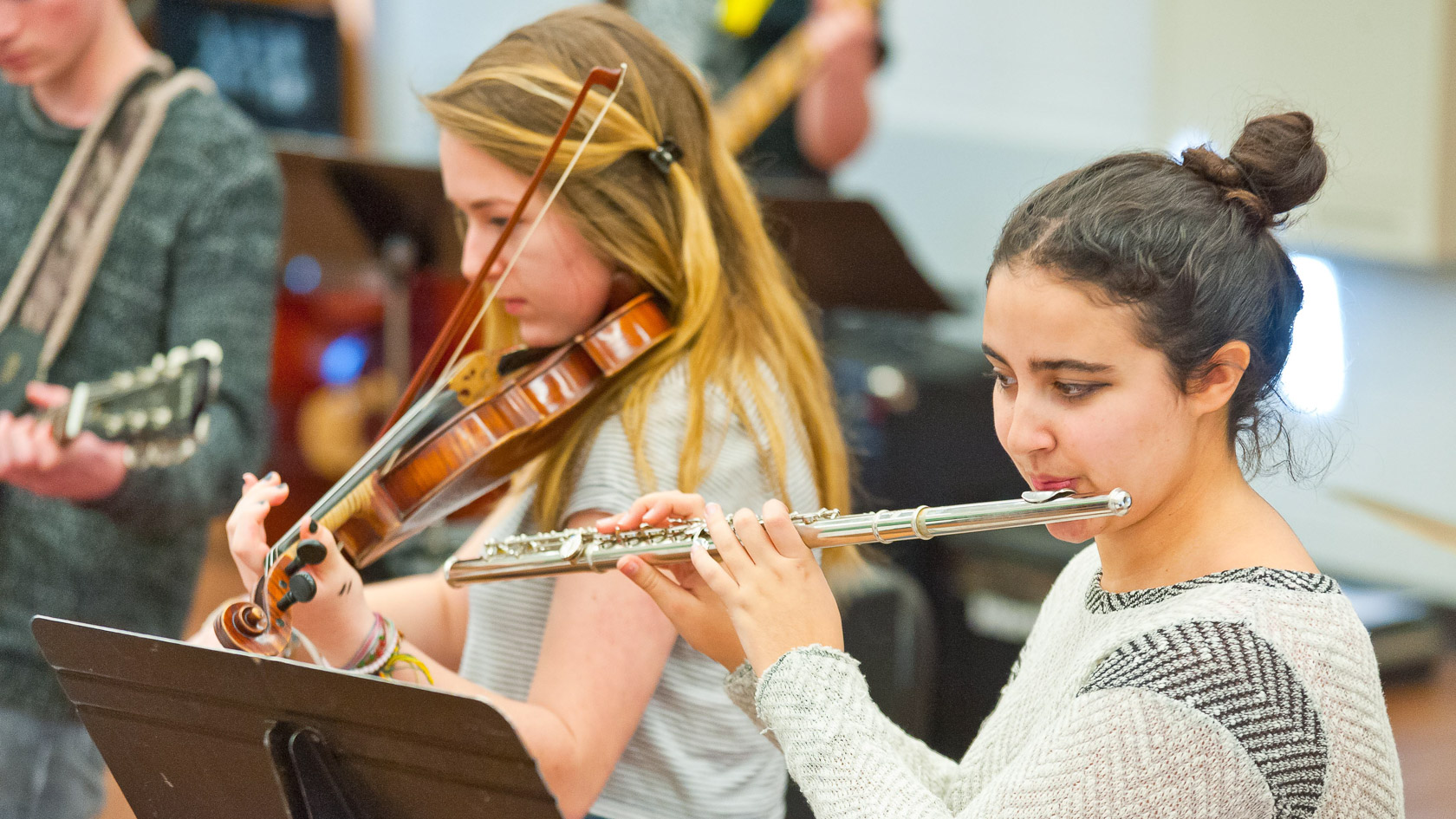 Student playing the flute in an orchestra practice