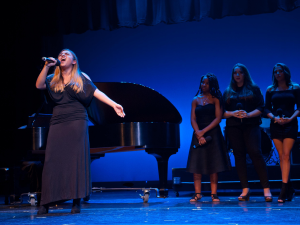 Female student singing on stage with backup singers and piano behind her
