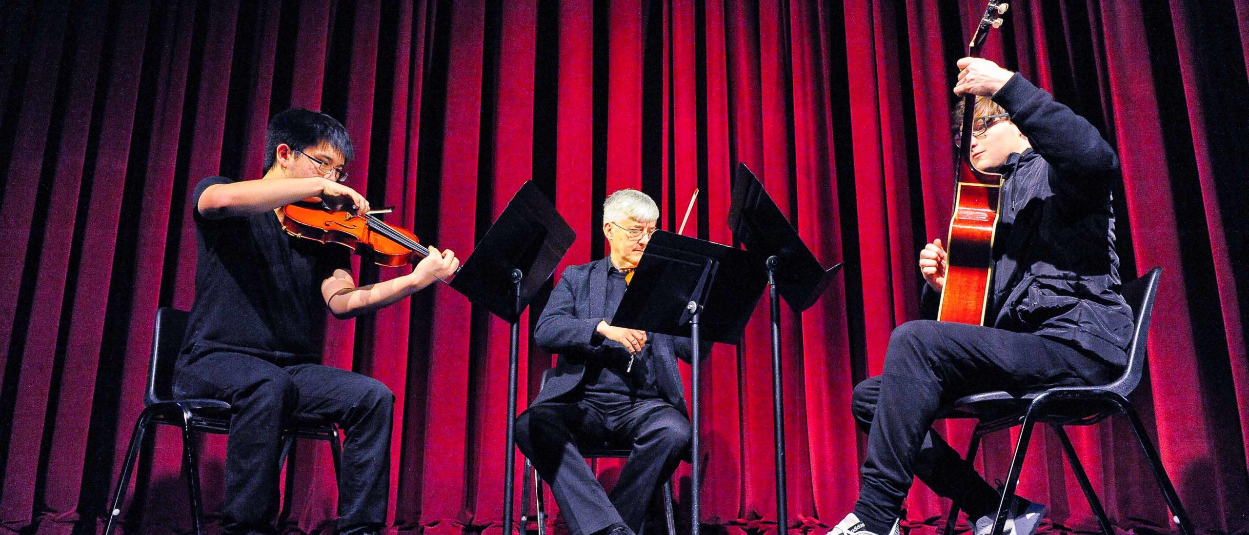 Two students an a faculty member playing string instruments on stage