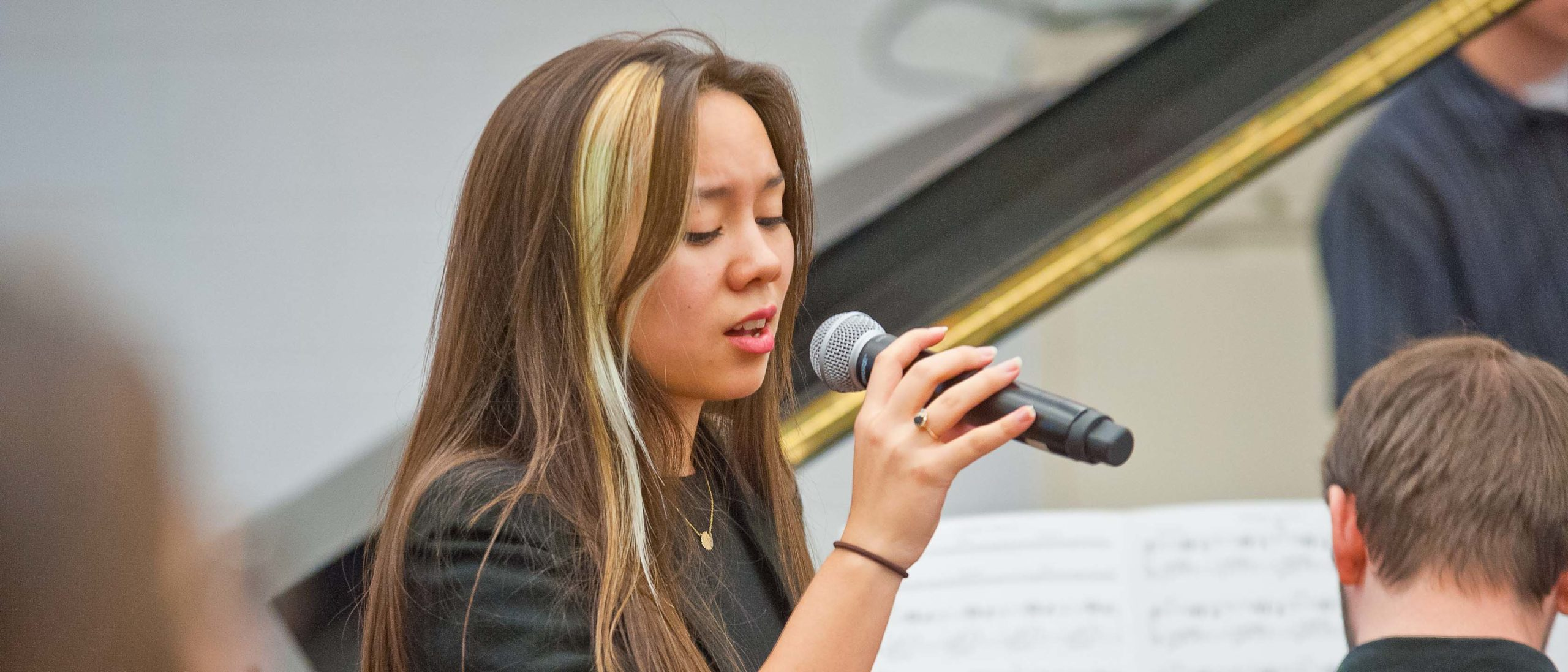 Girl student singing with a microphone in a classroom next to a piano
