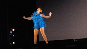 Solo female dancer in blue dress with may tassels performing