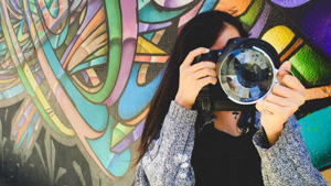 Student holding a camera to her face standing in front of a mural