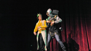 Two male students acting on stage during a performance