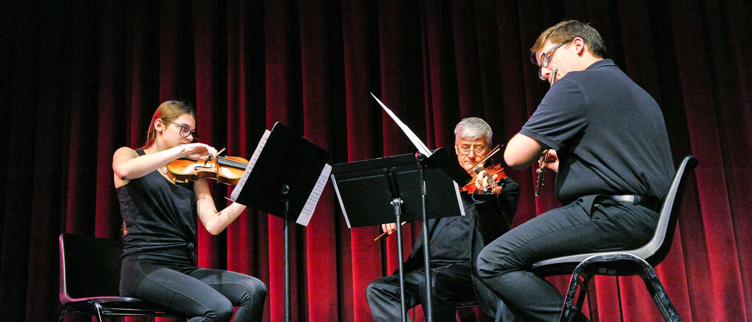 Two students and a faculty member playing string instruments on stage