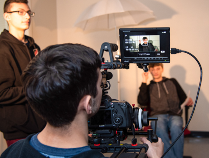 Male student behind the camera while filming a scene