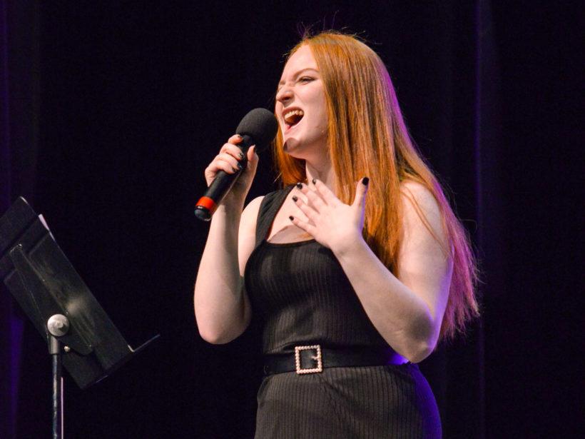 Female student singing on stage with a microphone