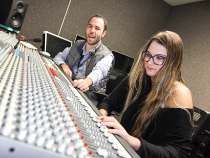 Sound engineer instructor teaching a student on the sound board