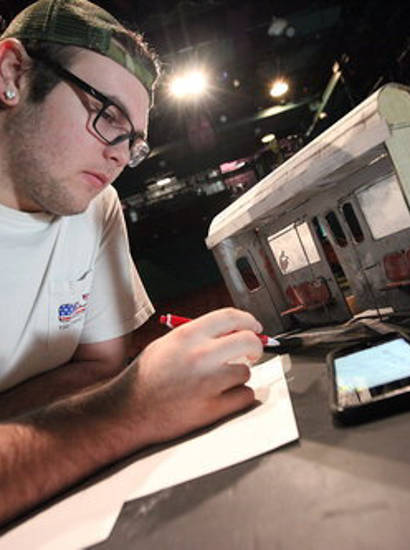 Male student sketching out set design ideas