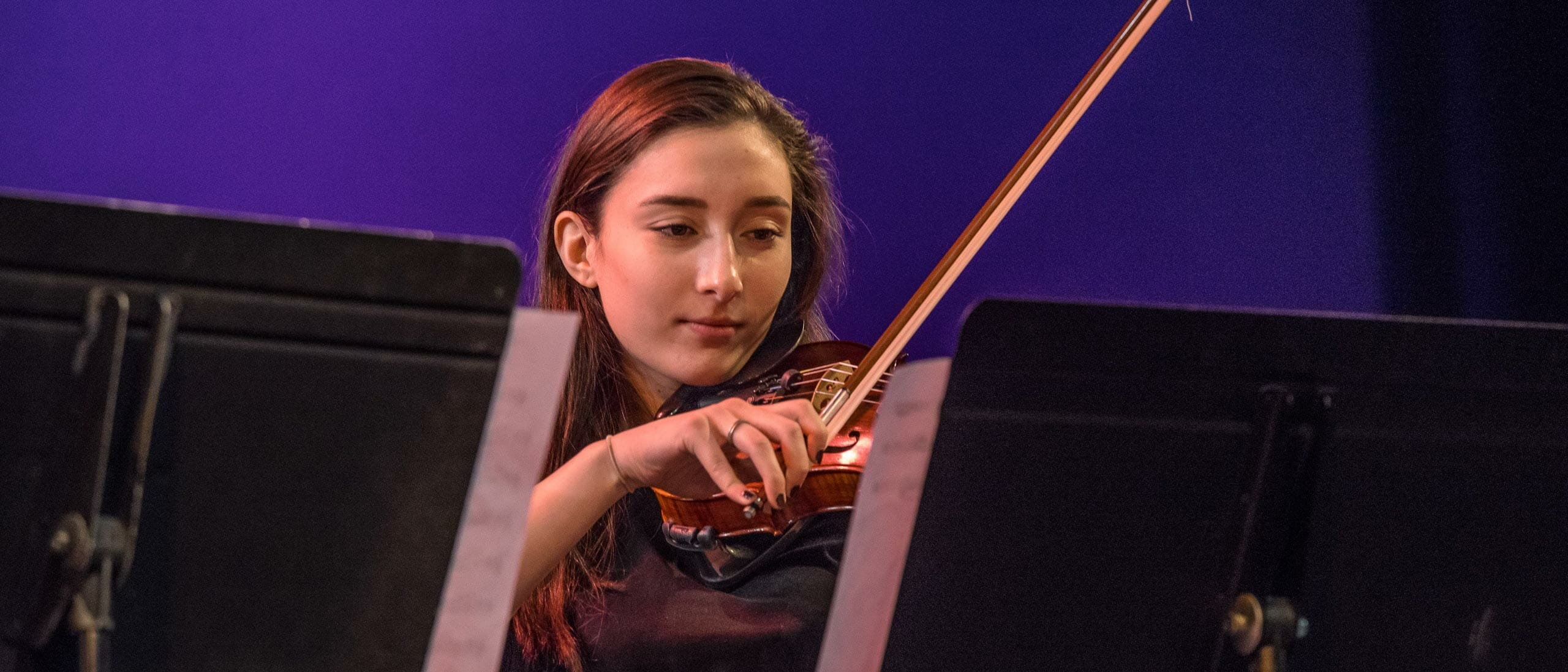 Female student playing the violin on stage