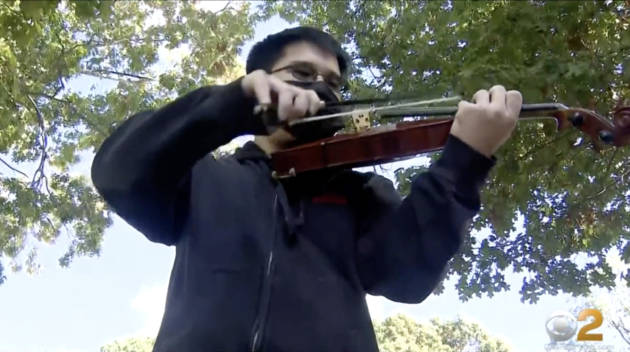 A boy with a mask playing the violin