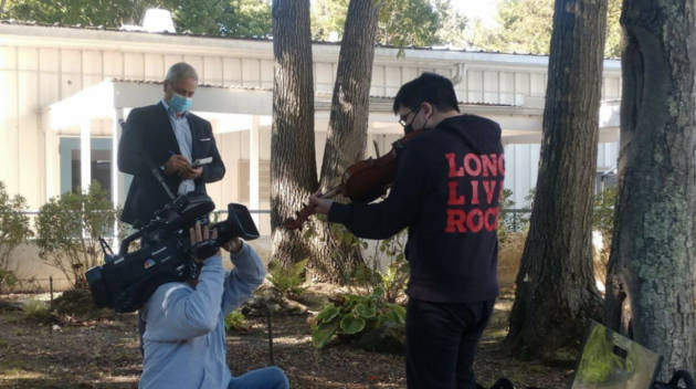 LIHSA student being filmed while playing the violin